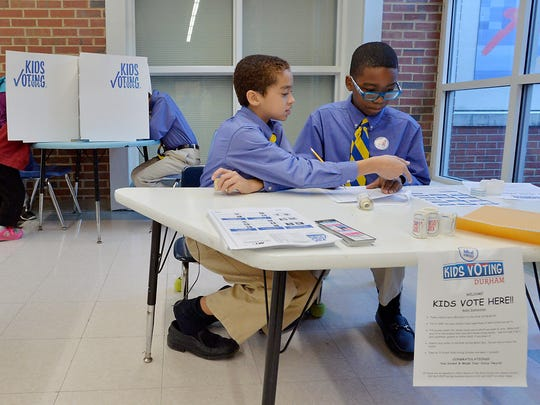 DURHAM, N.C - NOVEMBER 8:  Kids Vote polling attendants, Aiden Cushman (L), and Melton Henry, both 11, monitor the Kids Vote polling booths at E.K. Powe Elementary School on November 8, 2016 in Durham, North Carolina.