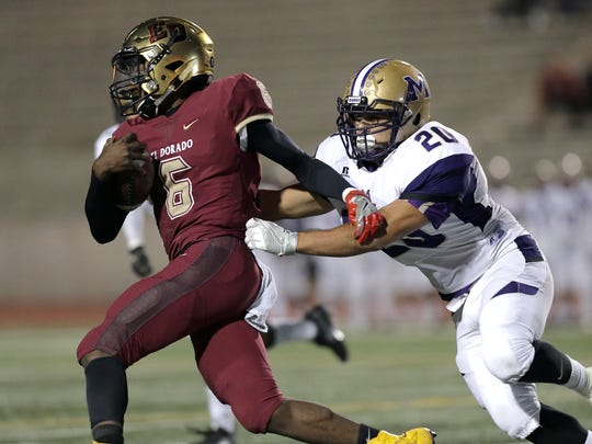 El Dorado quarterback Cedarious Barfield is chased out of the backfield by Midland linebacker Isaish Marquez Thursday in the first half of their bi-district game at the SAC.