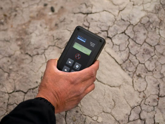 A geiger counter is used to measure radiation at an abandoned uranium mine in Cameron. Readings on the geiger counter were many times above background readings. There are 521 abandoned uranium mines on the Navajo Nation.
