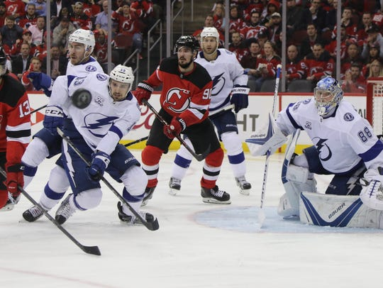 The puck flies in front of Nico Hischier of the Devils