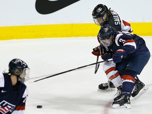 In this Tuesday, Dec. 5, 2017 photo, United States' Cayla Barnes (3) battles for the puck with Canada's Jillian Saulnier during the first period of a women's hockey game in Winnipeg, Manitoba. Days after watching the U.S. women lose 5-1 to Canada in Boston on Oct. 25, Barnes learned she was moving from the bleachers to the bench as a call-up to the national team with the chance to earn a roster spot for the 2018 Winter Olympics. The defender, who turned 18 in January, quickly withdrew from college to become the U.S. team's youngest player chasing an opportunity that had seemed four years away. (John Woods/The Canadian Press via AP)