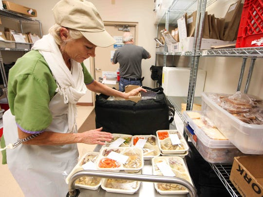Diana Ferrara of Newark packs hot meals into deliver bags. The Newark Senior Center prepares dozens of meals every day to be delivered in its Meals on Wheels program.