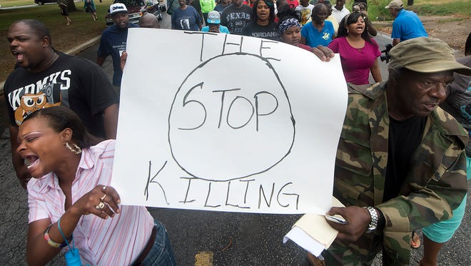 K.K. Davis, left, and Tommy Jones of Hearne, Texas, carry a sign with other protesters outside the Hearne police department to protest the shooting of a 93-year-old resident in her home.