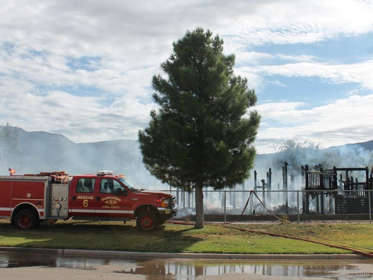 Firefighters continue spraying the remains of Kids Kingdom after containing most of the fire.
