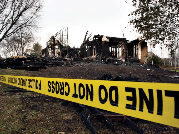 Fire investigators work at the scene of a fatal fire