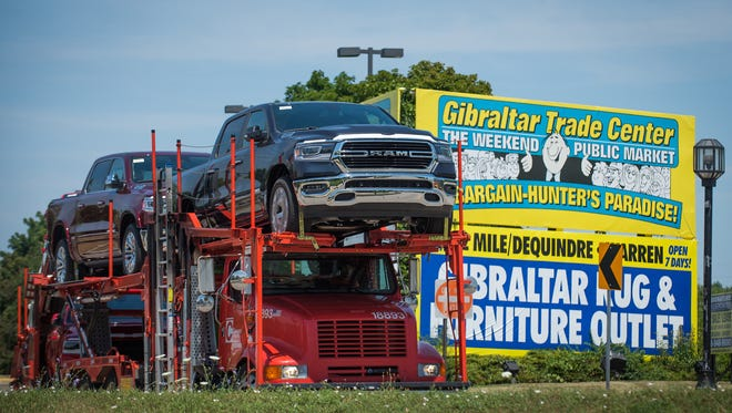 A truck transports several Ram trucks from the former Gibraltar Trading Center in Mount Clemens, Mich. on Thursday, July 19, 2018.