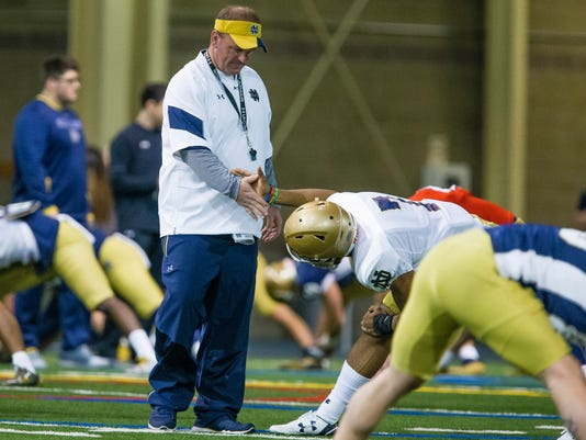 In this March 24, 2017, photo, Notre Dame defensive coordinator Mike Elko high fives Nick Watkins during NCAA college football practice at the Loftus Sports Center in South Bend, Ind. Elko, the 39-year-old hired from Wake Forest this offseason, has taken his Fighting Irish players into something of a time machine, harping on the basics early instead of scheme as the defense looks to rebound from a nightmarish 2016 that saw its previous coordinator lose his job in the season's first month. (Michael Caterina/South Bend Tribune via AP)