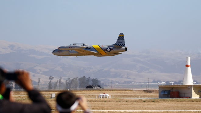 """Spectators look on as Gregory """"Wired"""" Colyer performs in a T-33 Shooting Star during the 37th annual California International Airshow, Salinas at the Salinas Municipal Airport on Saturday, September 30. 2017 in Salinas, Calif. Vernon McKnight/for The Californian"""
