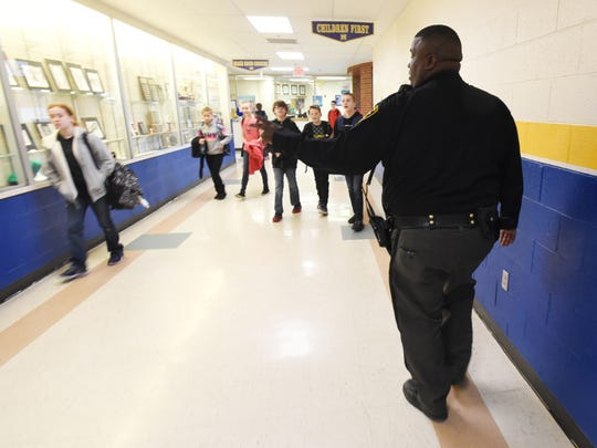 Maysville Local Schools resource officer John Howe waves to a student while walking the halls at Maysville's 6-12 building. Howe'sjob is to monitor the high school and middle school for suspicious activity, make sure nobody is where they aren't supposed to be and that all the doors that are supposed to be locked are locked.