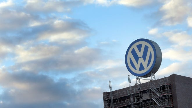 A giant logo of the German car manufacturer Volkswagen is pictured on top of a company's factory building in Wolfsburg, Germany, Saturday, Sept. 26, 2015.