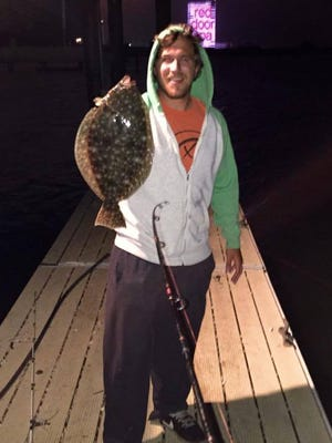 """Matthew Charles with a nice 19.75"""" off a South Jersey dock at night."""