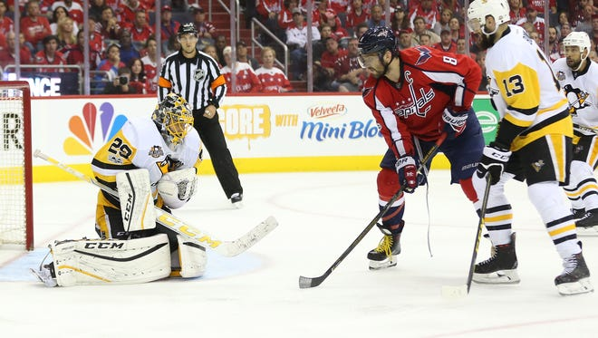 Pittsburgh Penguins goalie Marc-Andre Fleury makes a save in front of the Washington Capitals' Alex Ovechkin.