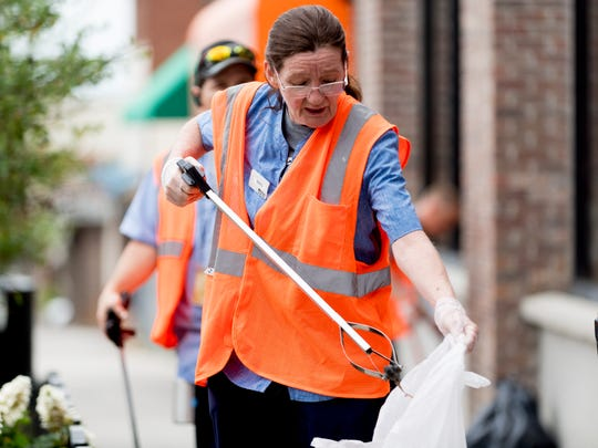 Rashell Holley, from the Hilton Garden Inn, cleans up trash during a Cumberland Avenue Cleanup event in Knoxville, Tennessee on Tuesday, May 22, 2018. The Cumberland Avenue Merchants Association (CAMA) teamed with Keep Knoxville Beautiful and the City of Knoxville to clean up the Cumberland Ave thoroughfare.