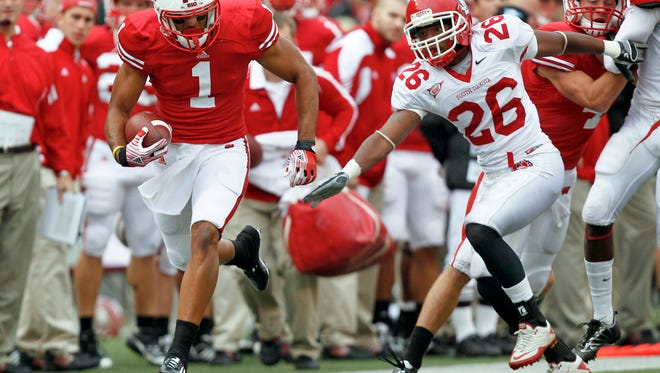 Wisconsin wide receiver Nick Toon (1) runs past South Dakota cornerback Aaron Swift (26) on the way to a touchdown during the first half of an NCAA college football game Saturday, Sept. 24, 2011, in Madison, Wis. (AP Photo/Andy Manis)