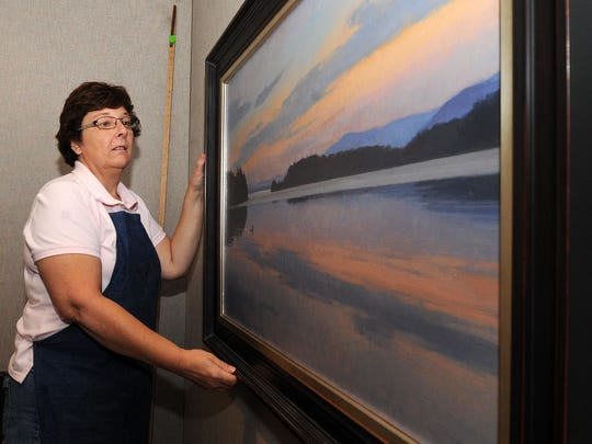 """In this 2011 file photo, curator Jane Weinke hangs up artworks for the annual """"Birds in Art"""" exhibit at the Woodson Art Museum in Wausau."""