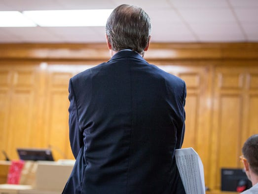 Defense attorney Thomas Wilmouth, folds his arms while