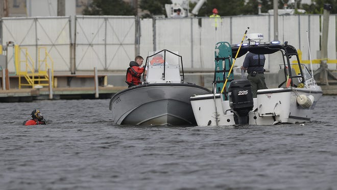 Members of the Winnebago County Sheriff's Department dive team search the Fox River where a helicopter crashed Saturday, June 9, 2018, in Oshkosh.