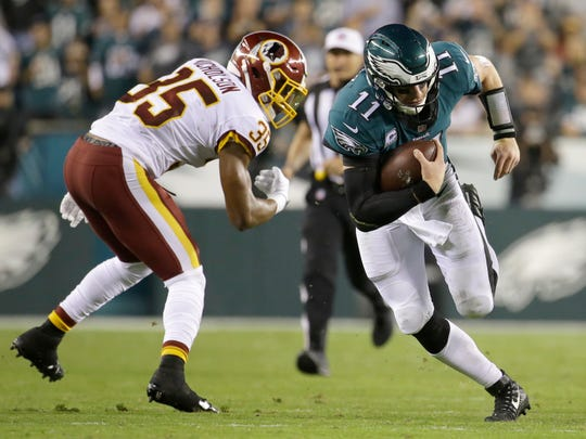 Philadelphia Eagles quarterback Carson Wentz (11) runs for yardage as Washington Redskins strong safety Montae Nicholson (35) tries to make a hit during the second half of an NFL football game, Monday, Oct. 23, 2017, in Philadelphia. (AP Photo/Michael Perez)