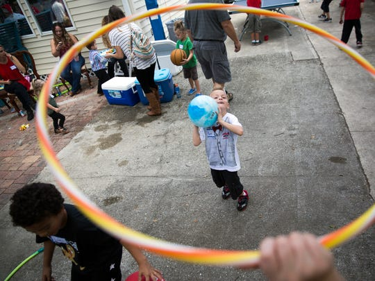 Taylor Erschen, 4, from Cape Coral, throws a ball as Emma Merz, 8, lifts the hula hoop high and higher during the first holiday party at Valerie's House in Fort Myers on Saturday, December 17, 2016. Valerie's House, which opened in January, provides a platform for the community to come together, grieve and openly talk about losing a loved one.
