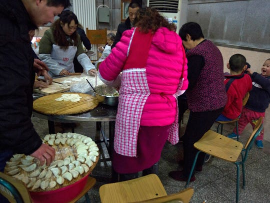 Children play as villagers gather to make dumplings ahead of the Chinese lunar new year at a village on the outskirts of Beijing, China, Thursday, Jan. 26, 2017.
