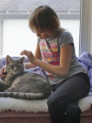 Makayla Zavrl, 9, plays with her cat at her home Tuesday
