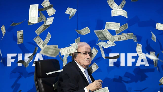 This file photo taken on July 20, 2015 shows then FIFA president Sepp Blatter looking on as fake dollar notes fly around him, thrown by a British comedian during a press conference at the FIFA world-body headquarter's in Zurich.  Former FIFA President Sepp Blatter and two deputies 'enriched themselves' with $80 million, the FIFA announced on June 3, 2016.