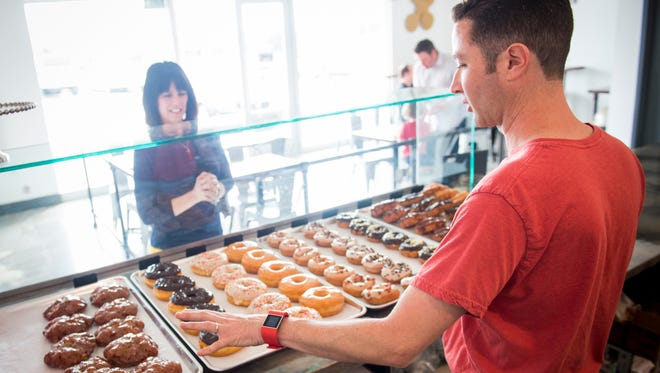 Co-owner Jimmy Wooten describes the different doughnuts offered at Status Dough on Monday, March 27, 2017. The doughnut shop offers a variety of donuts, such as cake doughnuts, yeast doughnuts, jelly doughnuts and gluten-free doughnuts.