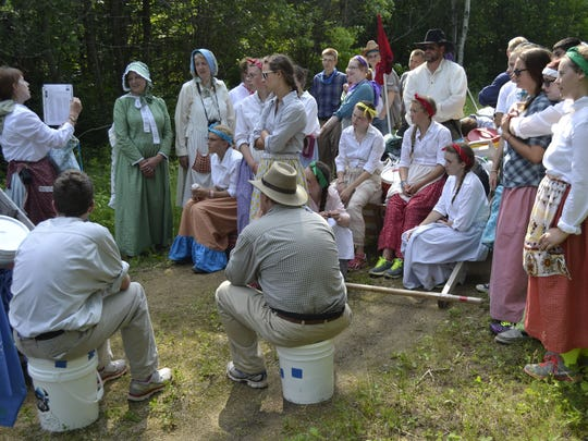 Adult leader Janet Hyden, top left, of Green Bay tells the story of an 1800s Mormon pioneer during a stop on Mountain-Bay Trail near Shawano. About 60 teenagers from The Church of Jesus Christ of Latter-day Saints' Green Bay Stake participated in the two-day trek of nearly 20 miles.