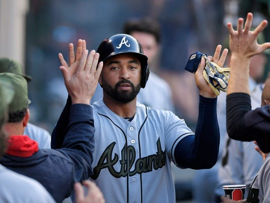 Atlanta Braves' Matt Kemp is congratulated by teammates after scoring on a ball hit by Tyler Flowers during the third inning of a baseball game against the Los Angeles Angels, Monday, May 29, 2017, in Anaheim, Calif. Angels second baseman Cliff Pennington was charged with an error while fielding the ball. (AP Photo/Mark J. Terrill)