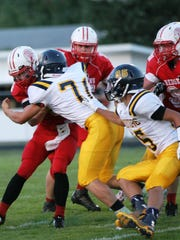 Woodmore's Dustin Haar (71) and Jeremy Cuevas (85) pursue a Port Clinton runner in the 2014 season opener.