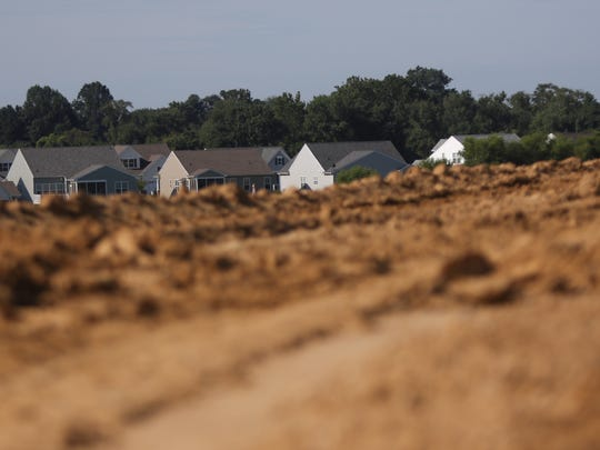 Homes in the Spring Arbor neighborhood peak out from behind a visual earth berm built alongside U.S. 301 toll road to site of the new highway.