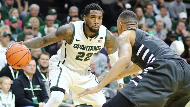 Branden Dawson of the Michigan State Spartans drives to the basket against Femi Olujobi of the Oakland Golden Grizzlies on December 14, 2014 in East Lansing, Michigan.