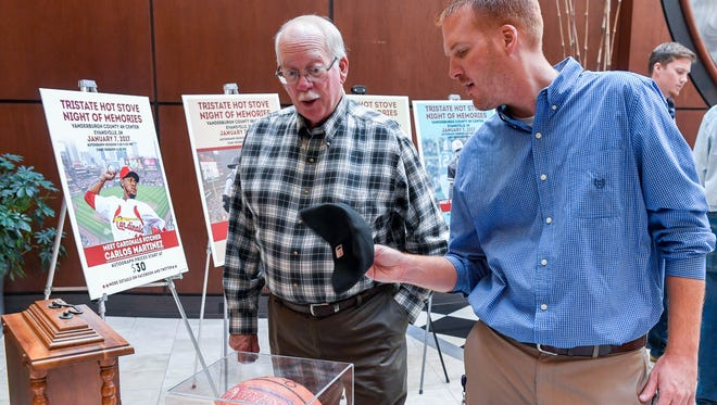 Steve Millay (left) and Ryan Berger examine autographed sports memorabilia following the Tri-State Hot Stove League press conference Wednesday promoting the Night of Memories annual charity fundraiser January 7 at the Vanderburgh 4-H Center, November 16, 2016.