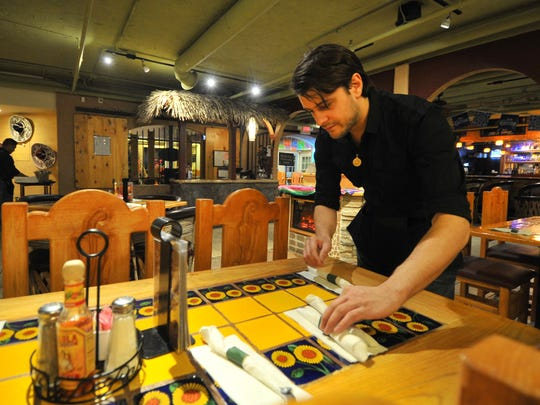 Waiter Allen Arnold, of Wausau, sets up a table Thursday in the downstairs dining area of Jalapenos Mexican Restaurante & Bar in downtown Wausau.