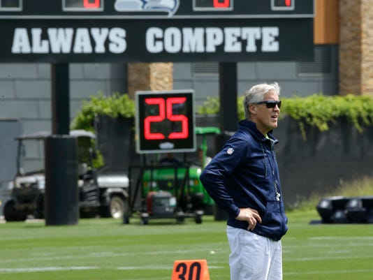 """Seattle Seahawks head coach Pete Carroll stands near a scoreboard that reads """"Always Compete,"""" during NFL football practice, Tuesday, June 6, 2017, in Renton, Wash. (AP Photo/Ted S. Warren)"""
