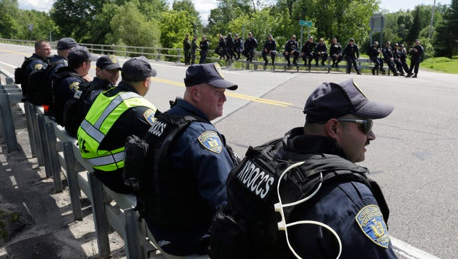New York State officers take a break from searching for convicted murderers Richard Matt and David Sweat, Friday, June 26, 2015, in Malone, N.Y.
