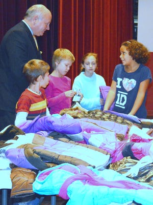 Five Star Bank Regional President Jeff Kenefick meets with students from Broadway Elementary School on Tuesday during a winter coat giveaway.