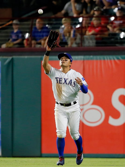 Texas Rangers right fielder Shin-Soo Choo, of South Korea, reaches to catch a fly-out by Seattle Mariners' Jean Segura in the seventh of a inning of a baseball game, Monday, July 31, 2017, in Arlington, Texas. (AP Photo/Tony Gutierrez)