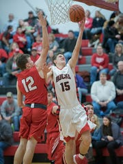 Buckeye Central's Max Loy goes up for a layup with Bucyrus' Ben Seibert defending him.