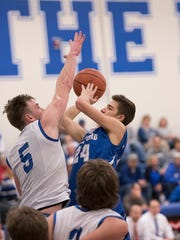 Wynford's Josh Crall puts up a shot with Crestline's Zach Gregory's hand in his face.