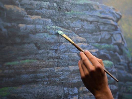 Aaron Wolken carefully paints rocks on a cliff on part