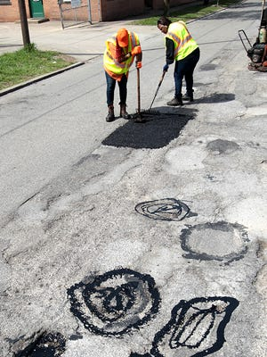 """Swirls of hot tar mark potholes to be filled on Chandler Street, Madisonville, as Cincinnati structure maintenance workers (cq) Anetra Reeves (left) uses a tamper to level ashphalt in a newly-filled pothole and  Brenda Harris rakes the asphalt flat.  The tar on the potholes in the foreground helps bond the fresh asphalt to the old road surface. The city has begun a """"pothole blitz"""" and is asking residents to report potholes. Last year city workers filled 49,000 potholes.  The Enquirer/Patrick Reddy"""
