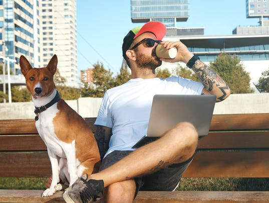 Guy on laptop drinking coffee with his dog