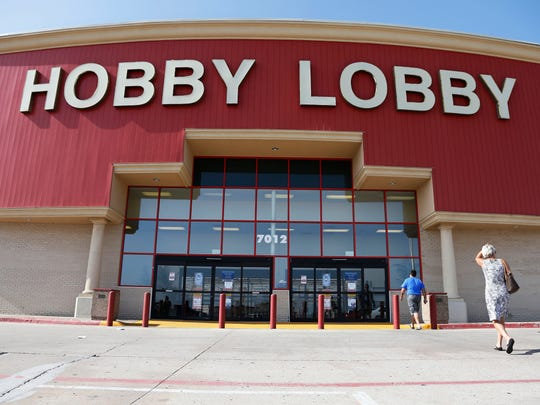 FILE - In this Monday, June 30, 2014, file photo, customers walk to a Hobby Lobby store in Oklahoma City. A Hobby Lobby spokesman told The Associated Press on May 10, 2017, that a report stating the company was considering going out of business is not true. (AP Photo/Sue Ogrocki, File)
