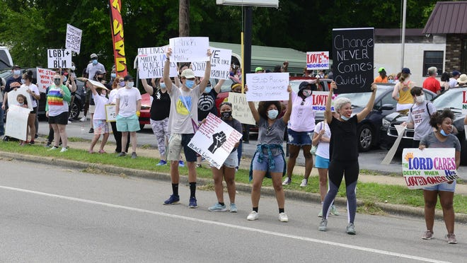 Protesters hold up signs along Meighan Boulevard in Alabama City before a Black Lives Matter march June 7.