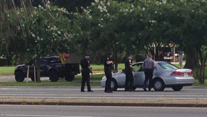 Authorities talk to the driver of a car near an area where several officers were shot while on duty less than a mile from police headquarters on July 17, 2016, in Baton Rouge, La.