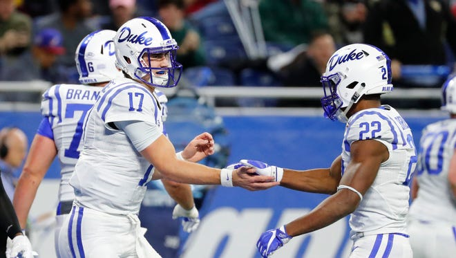 Duke Blue Devils quarterback Daniel Jones (17) celebrates a touchdown with running back Brittain Brown (22) in the first quarter against the Northern Illinois Huskies in the 2017 Quick Lane Bowl at Ford Field.