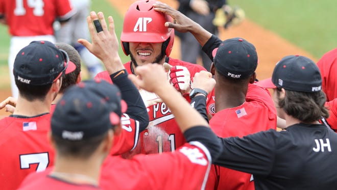 Austin Peay State University junior Dre Gleason (11) gets his helmet pushed down by teammates as they congratulate him after he scored during their game against Eastern Illinois University on March 11, 2016. Austin Peay won the game 5-3.