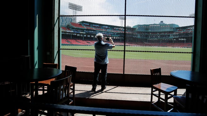 In this June 25, 2020, photo, a reporter photographs the view of the baseball field at Fenway Park from the Bleacher Bar in Boston. Tucked under the center field seats at Fenway Park, down some stairs from Lansdowne Street in an area previously used as the visiting team's batting cage, is a sports bar that is preparing to reopen from the coronavirus shutdown. If Major League Baseball's plans remains on schedule, it may be one of the few places fans will be able to watch a game in person this season.