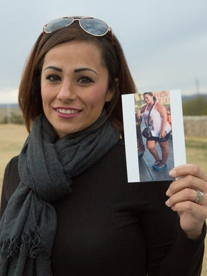 Brittney Lozano, holds up a photo of herself before her bariatric surgery.